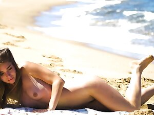 Petite convocation MILF Lily Chey suntanning on the beach